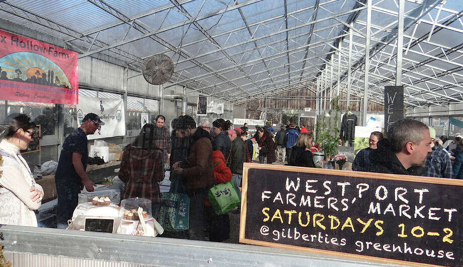 Shoppers browse the Westport Farmers Market at Gilberties Greenhouse -- its winter season quarters -- on Saturday morning.  Westport CT 1/5/13 Photo: Mike Lauterborn / Westport News contributed