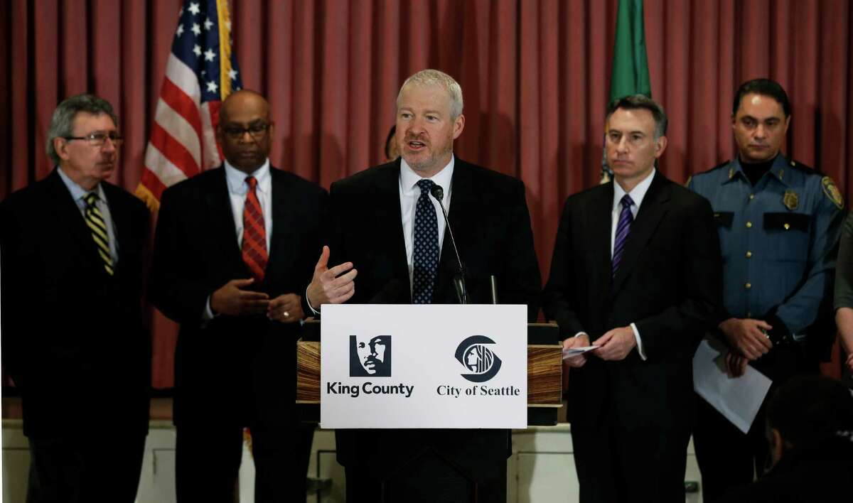 Seattle Mayor Mike McGinn, center, speaks Jan. 8, at a news conference to announce a new gun buyback program that will begin later in January. Behind him, from left, are former Seattle mayors Charles Royer, and Norm Rice, King Co. Executive Dow Constantine, and Seattle Deputy Police Chief Nick Metz. (AP Photo/Ted S. Warren)