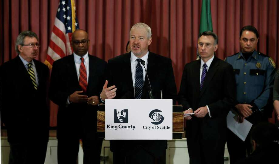 Seattle Mayor Mike McGinn, center, speaks Jan. 8,  at a news conference to announce a new gun buyback program that will begin later in January. Behind him, from left, are former Seattle mayors Charles Royer, and Norm Rice, King Co. Executive Dow Constantine, and Seattle Deputy Police Chief Nick Metz. (AP Photo/Ted S. Warren) Photo: Associated Press