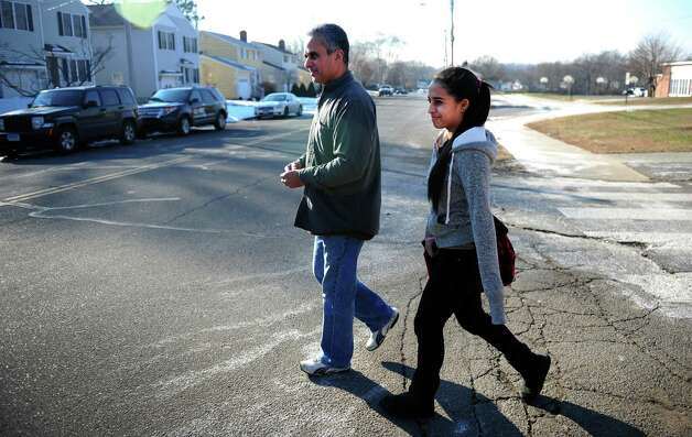 Jose Carlos Santos and his daughter Rayanne Santos, 13, leave Wooster Middle School in Stratford, Conn. following a lockdown Tuesday, Jan. 8, 2013. Authorities apprehended four men, two carrying what are believed to be hi-powered pellet rifles in the woods behind the school. Photo: Autumn Driscoll / Connecticut Post
