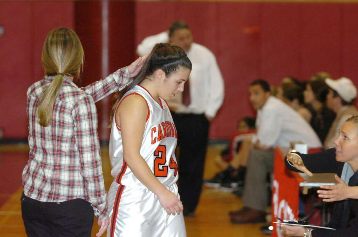 Greenwich Coach Danielle Morgan pats Jessica Fiscella as she heads to the bench after she fouled out late in the game as Greenwich hosts Fairfield Warde High School in a girls basketball game Tuesday evening, Dec. 22, 2009. Warde won 39-37.