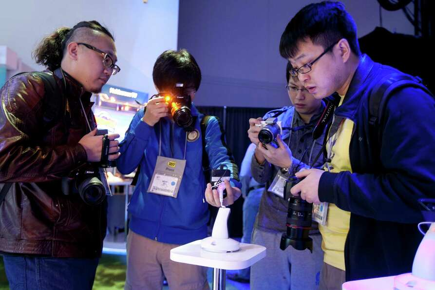 Attendees take photographs of a reference design smartphone intended for emerging markets at the Int