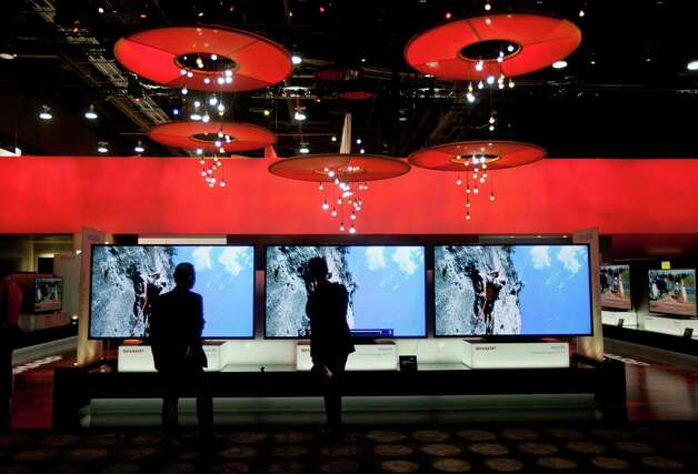 Attendees look at Sharp Corp. 90-inch televisions during the 2013 Consumer Electronics Show in Las Vegas, Nevada, U.S., on Tuesday, Jan. 8, 2013. The 2013 CES trade show, which runs until Jan. 11, is the world's largest annual innovation event that offers an array of entrepreneur focused exhibits, events and conference sessions for technology entrepreneurs. Photographer: Andrew Harrer/Bloomberg Photo: Andrew Harrer, Bloomberg / © 2013 Bloomberg Finance LP