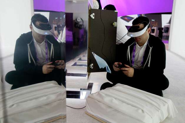 Andrey Pinero sets up a Sony Corp. Personal 3D Viewer headset during the 2013 Consumer Electronics Show in Las Vegas, Nevada, U.S., on Tuesday, Jan. 8, 2013. The 2013 CES trade show, which runs until Jan. 11, is the world's largest annual innovation event that offers an array of entrepreneur focused exhibits, events and conference sessions for technology entrepreneurs. Photographer: Andrew Harrer/Bloomberg *** Local Caption *** Andrey Pinero Photo: Andrew Harrer, Bloomberg / © 2013 Bloomberg Finance LP