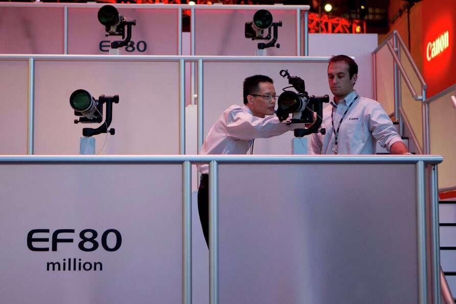 Canon Corp. representatives look at cameras during the 2013 Consumer Electronics Show in Las Vegas,