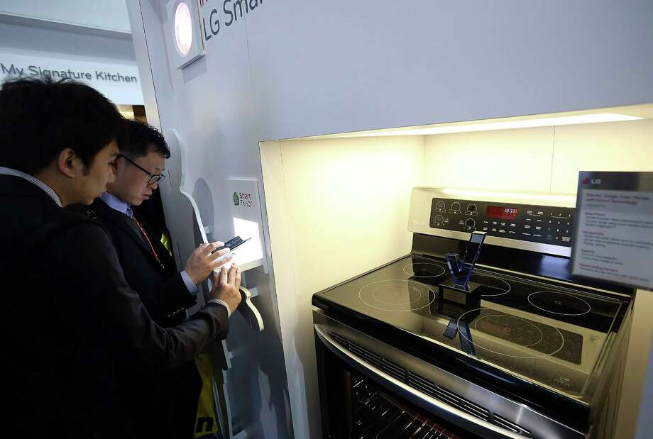 LAS VEGAS, NV - JANUARY 08:  Attendees inspect an LG Smart Oven during the 2013 International CES at the Las Vegas Convention Center on January 8, 2013 in Las Vegas, Nevada. CES, the world's largest annual consumer technology trade show, runs from January 8-11 and is expected to feature 3,100 exhibitors showing off their latest products and services to about 150,000 attendees. Photo: Justin Sullivan, Getty Images / 2013 Getty Images