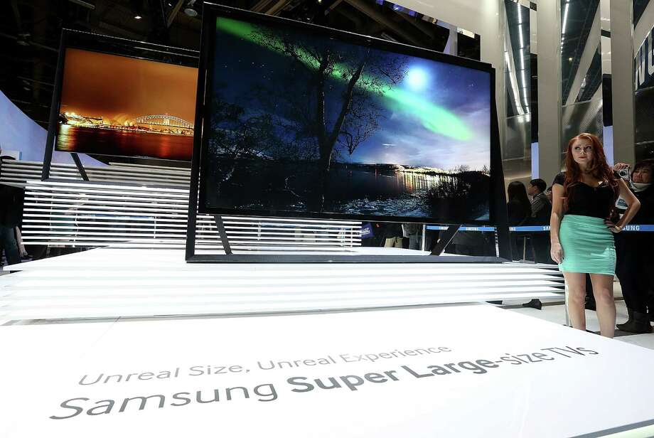 LAS VEGAS, NV - JANUARY 08:  A model stands next to a display of new large format Samsung televisions during the 2013 International CES at the Las Vegas Convention Center on January 8, 2013 in Las Vegas, Nevada. CES, the world's largest annual consumer technology trade show, runs from January 8-11 and is expected to feature 3,100 exhibitors showing off their latest products and services to about 150,000 attendees. Photo: Justin Sullivan, Getty Images / 2013 Getty Images