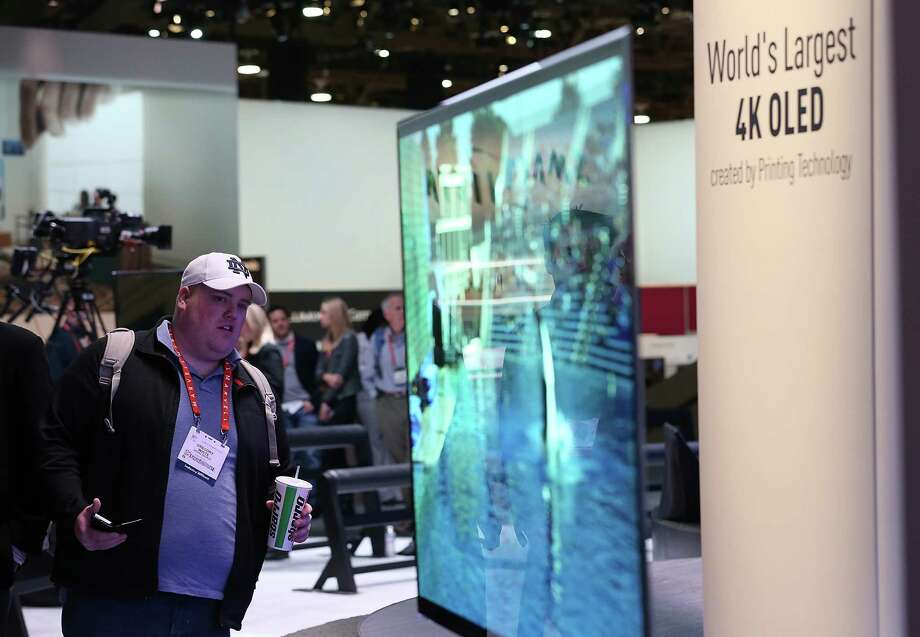 "LAS VEGAS, NV - JANUARY 08:  An attendee looks at a display of the Panasonic 4K OLED 56"" television during the 2013 International CES at the Las Vegas Convention Center on January 8, 2013 in Las Vegas, Nevada. CES, the world's largest annual consumer technology trade show, runs from January 8-11 and is expected to feature 3,100 exhibitors showing off their latest products and services to about 150,000 attendees. Photo: Justin Sullivan, Getty Images / 2013 Getty Images"