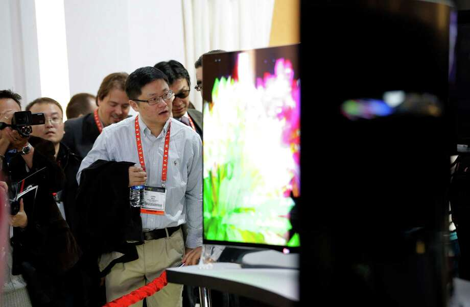 Show attendees look at curved OLED displays at the LG booth at the International Consumer Electronics Show in Las Vegas, Tuesday, Jan. 8, 2013. (AP Photo/Jae C. Hong) Photo: Jae C. Hong, Associated Press / AP
