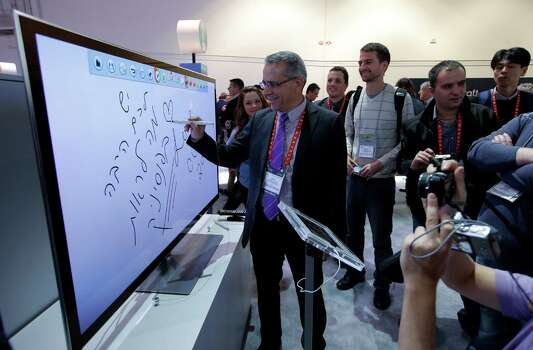 Moti Elmaliach, center, of Israel, writes on a display using Panasonic's electronic touch pen at the Panasonic booth at the International Consumer Electronics Show in Las Vegas, Tuesday, Jan. 8, 2013. (AP Photo/Jae C. Hong) Photo: Jae C. Hong, Associated Press / AP