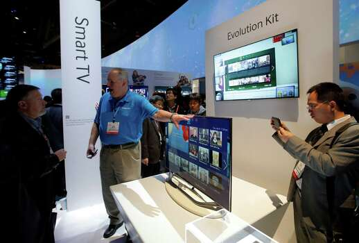 Show attendees check out Samsung smart TVs at the Samsung booth at the International Consumer Electronics Show in Las Vegas, Tuesday, Jan. 8, 2013. (AP Photo/Jae C. Hong) Photo: Jae C. Hong, Associated Press / AP
