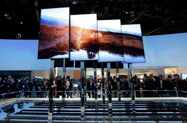 Show attendees look at an installation made with smart TVs at the Samsung booth at the International Consumer Electronics Show in Las Vegas, Tuesday, Jan. 8, 2013. (AP Photo/Jae C. Hong) Photo: Jae C. Hong, Associated Press / AP