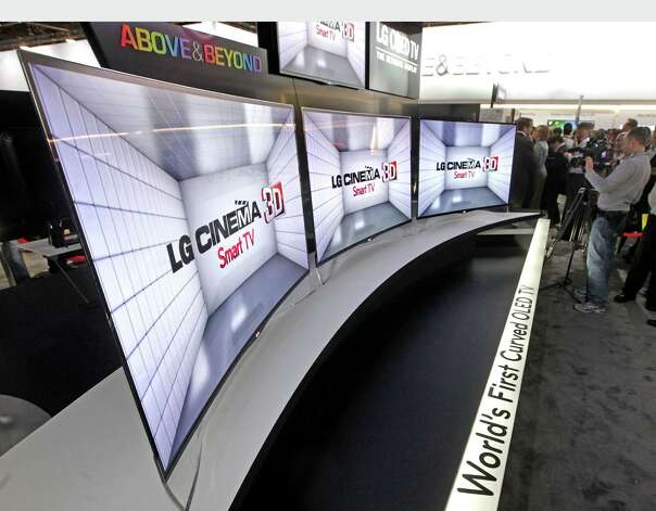 Global technology leader LG Electronics shows visitors its first curved OLED TV at the 2013 Consumer Electronics Show in Las Vegas.  (PRNewsFoto/LG Electronics) Photo: Associated Press / LG ELECTRONICS