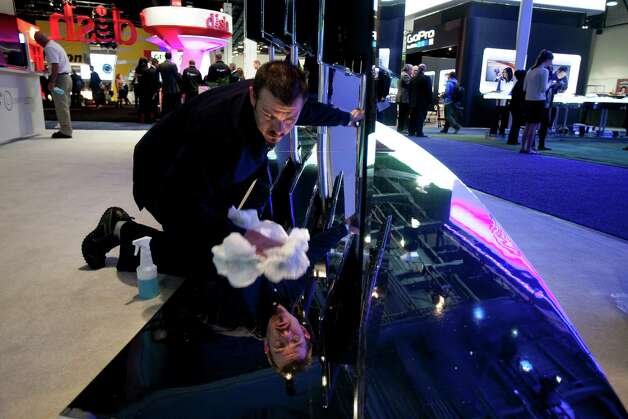 A worker cleans a display at the Hisense Electric Co. Ltd. booth during the 2013 Consumer Electronics Show in Las Vegas, Nevada, U.S., on Tuesday, Jan. 8, 2013. The 2013 CES trade show, which runs until Jan. 11, is the world's largest annual innovation event that offers an array of entrepreneur focused exhibits, events and conference sessions for technology entrepreneurs. Photographer: Andrew Harrer/Bloomberg Photo: Andrew Harrer, Bloomberg / © 2013 Bloomberg Finance LP