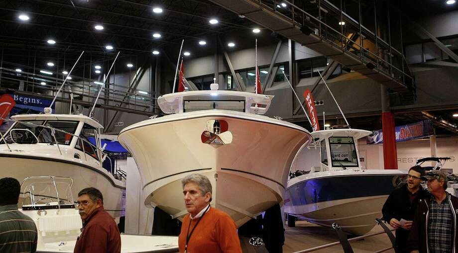 Attendees walk past boats during the 56th Annual Houston International Boat, Sport & Travel Show at Reliant Center Monday, Jan. 7, 2013, in Houston. Photo: Johnny Hanson, Houston Chronicle / © 2012  Houston Chronicle
