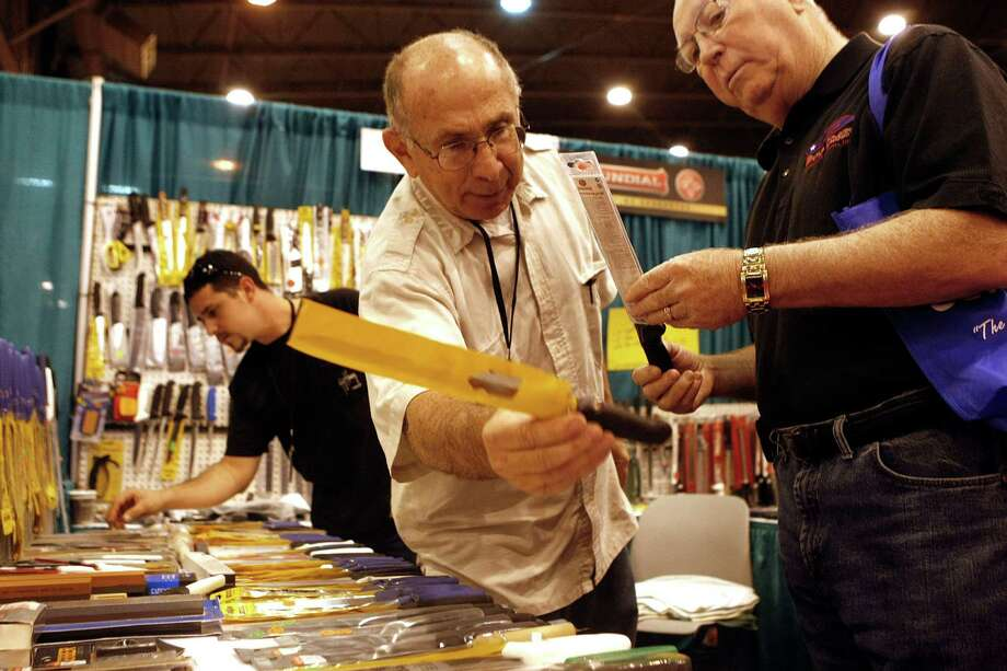 Larry Cohen with I and L Specialty Cutlery out of Sarasota, Fla., sells Jim Vogt of Klein a set of knives at the 56th Annual Houston International Boat, Sport & Travel Show at Reliant Center Monday, Jan. 7, 2013, in Houston. Photo: Johnny Hanson, Houston Chronicle / © 2012  Houston Chronicle