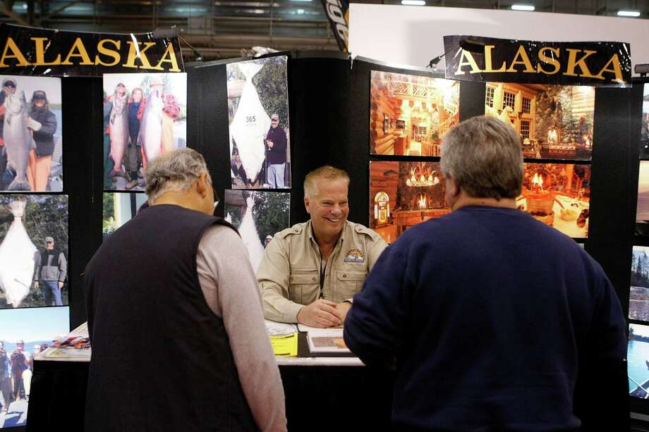 Steven Moe, with the Deep Creek Fishing Club out of Ninilchik, Alak., talks with Mike Lewis, right, of Deer Park and Roy Iltis of La Porte during the 56th Annual Houston International Boat, Sport & Travel Show at Reliant Center  Monday, Jan. 7, 2013, in Houston. Photo: Johnny Hanson, Houston Chronicle / © 2012  Houston Chronicle