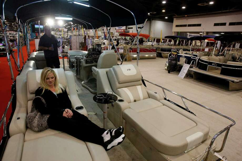 Nicole Murphy sits on a Avalon Deco Series Ambassador 27' pontoon boat at the Texas Marine exhibit while attending the 56th Annual Houston International Boat, Sport & Travel Show with her father Mickey Murphy, back, at Reliant Center  Monday, Jan. 7, 2013, in Houston. Photo: Johnny Hanson, Houston Chronicle / © 2012  Houston Chronicle