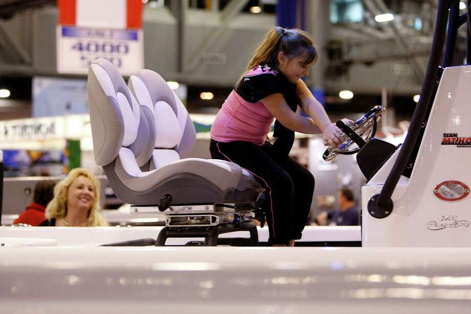 With her mother, Michelle Jenkins looking on, Montana Jenkins pretends to drive a a Blue Wave 2400 Pure Bay at the Mt. Houston Marine exhibit during the 56th Annual Houston International Boat, Sport & Travel Show at Reliant Center Monday, Jan. 7, 2013, in Houston. Photo: Johnny Hanson, Houston Chronicle / © 2012  Houston Chronicle