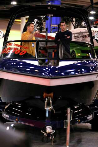 Tyler Ponder, right, of Deer Park looks at a Moomba Outback V boat with the help of Trey Tiller with Rinker's Boat World at the 56th Annual Houston International Boat, Sport & Travel Show  at Reliant Center Monday, Jan. 7, 2013, in Houston. Photo: Johnny Hanson, Houston Chronicle / © 2012  Houston Chronicle