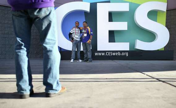 LAS VEGAS, NV - JANUARY 08:  Attendees take their photo in front of a sign as they arrive at the 2013 International CES at the Las Vegas Convention Center on January 8, 2013 in Las Vegas, Nevada. CES, the world's largest annual consumer technology trade show, runs from January 8-11 and is expected to feature 3,100 exhibitors showing off their latest products and services to about 150,000 attendees. Photo: Justin Sullivan, Getty Images / 2013 Getty Images
