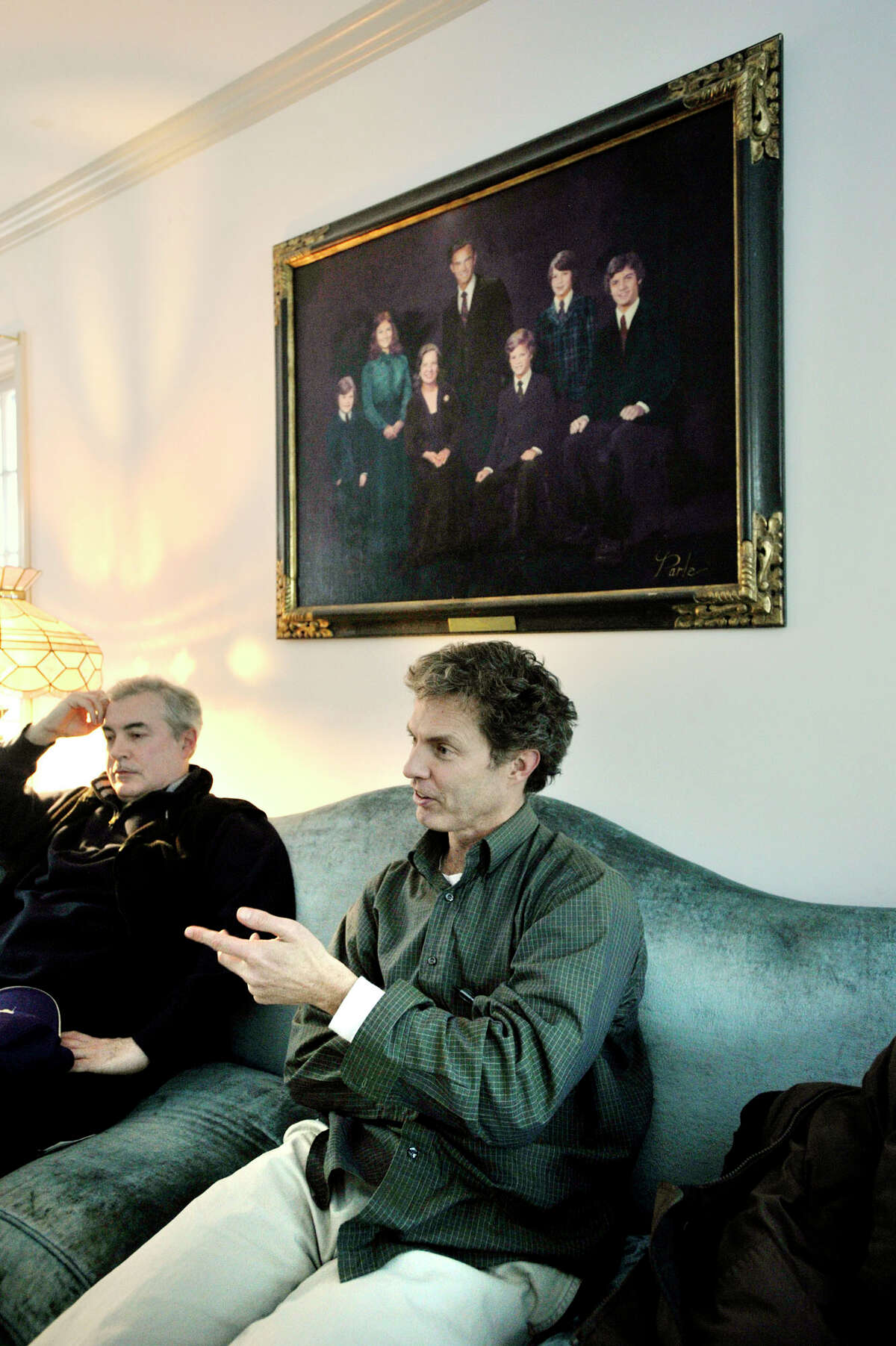 James Orr recalls stories about his mother, Annie Orr, underneath a family portrait in Annie's living room in Danbury. Annie, a prominent activist, died Monday. James' brother, Bill, is seen at left.