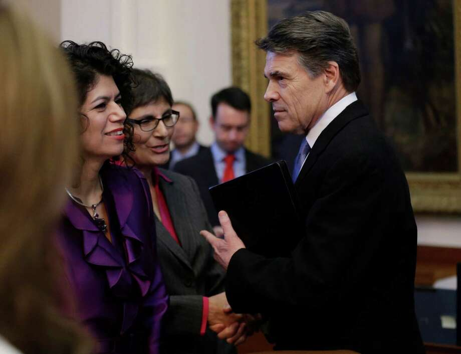 Texas Gov. Rick Perry, right, shakes hands after addressing the opening session of the 83rd Texas Legislature, Tuesday, Jan. 8, 2013, in Austin, Texas. (AP Photo/Eric Gay) Photo: Eric Gay, Associated Press / AP