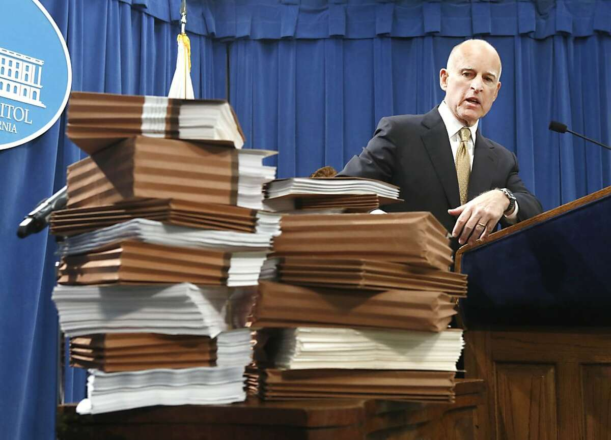 Gov. Jerry Brown gestures to a stack of reports on California prisons as he discuss his call for federal judges to return control of California prison to the state during a news conference at the Capitol in Sacramento, Calif., Tuesday, Jan. 8, 2013. Brown said that it is too dangerous for the state to further reduce its prison population as required by a federal court order. (Photo/Rich Pedroncelli)