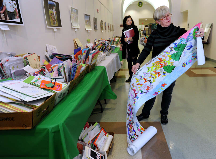 Jeanne Schneider, a retired Newtown Middle School teacher, reads a mural sent from Qeubec, Canada, and written in both French and English, in support of victims and families of the Sandy Hook shootings, Tuesday, January 8, 2013.  The main hall of the Newtown Town Hall is set up with tables full of messages from all over the world offering support and condolances. Photo: Carol Kaliff / The News-Times