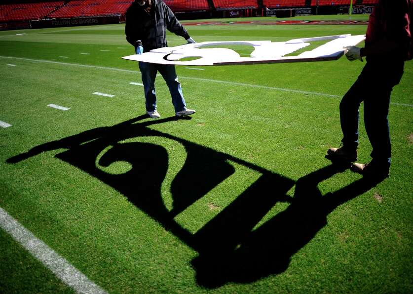 Members of the ground crew carry a large stencil across the field, which is used for painting the ya