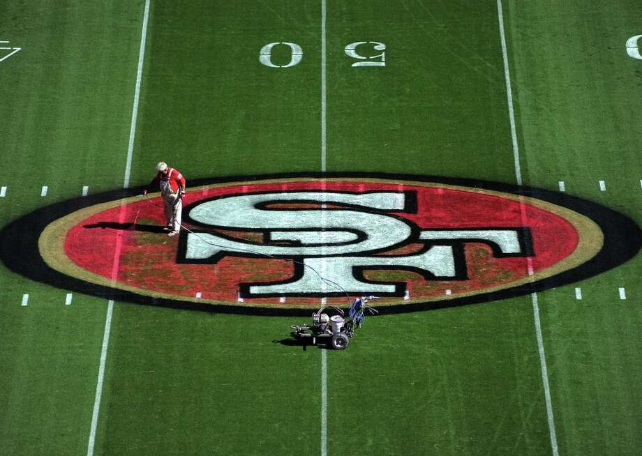 Head painter John Foote uses spray machine to paint the logo on the 50 yard line at the center of the field. The grounds crew is busy at work the day before the game painting the field in black, white, red and gold. Photo: Michael Short, Special To The Chronicle / ONLINE_YES