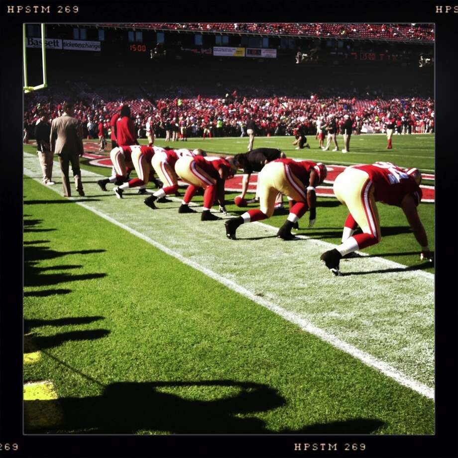 Players warm up at on the freshly painted field. Photo: Luanne Dietz, The Chronicle / ONLINE_YES