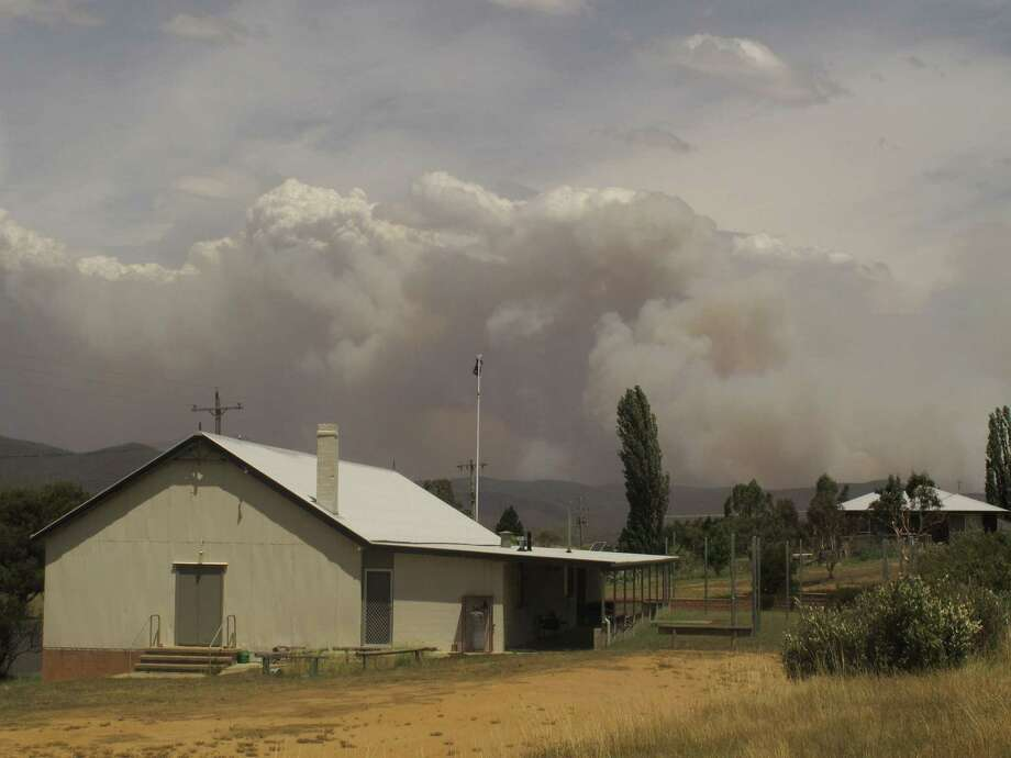 Smoke rises Tuesday from hills outside a village in New South Wales, Australia's most populous state, where summer wildfires have scorched some 74,000 acres. Photo: Rod McGuirk, STF / AP