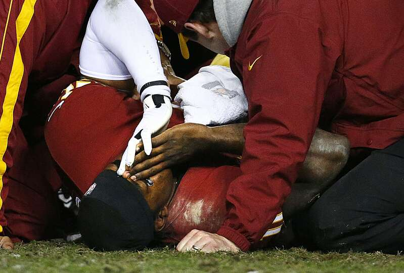 Washington Redskins quarterback Robert Griffin III lies on the ground  Sunday. Coach Mike Sh