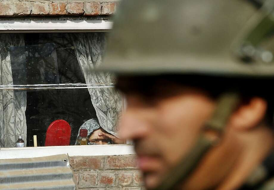 A Kashmiri woman peeks from her window as an policeman observes a protest near Srinagar, India. Photo: Mukhtar Khan, Associated Press