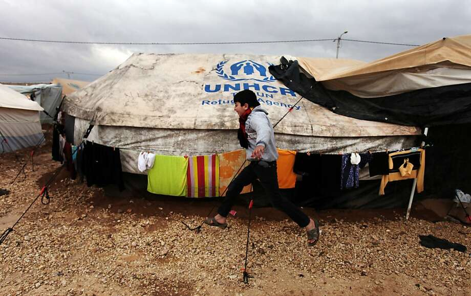 A Syrian refugee boy runs to his family tent at Zaatari Syrian refugee camp, near the Syrian border in Mafraq, Jordan. Refugees in the camp attacked aid workers, frustrated after cold winds swept away tents. Photo: Mohammad Hannon, Associated Press