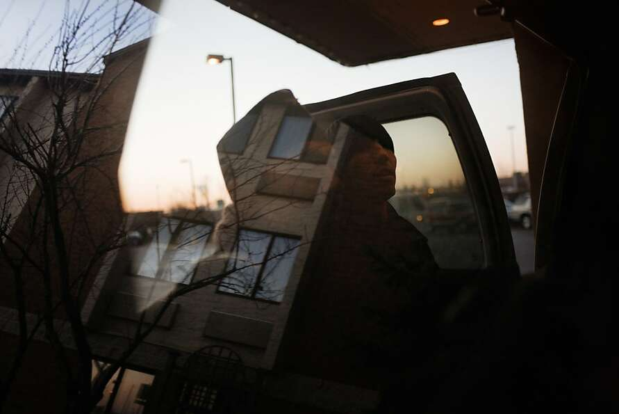 12/11/09, Newark, An IOM officer helps unloading the bags on the shuttle that has taken the refugees