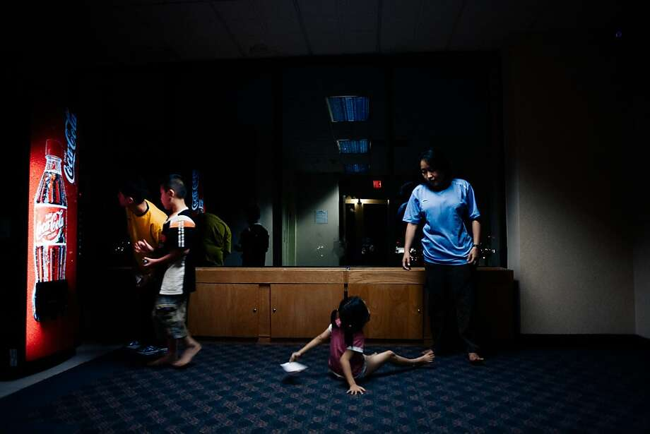 3/28/2008: Los Angeles, LAX: A family of  Burmese refugees hangs around a Coke vending machine on their first night in America. Photo: Gabriele Stabile