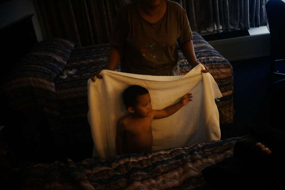 6/14/2010: Chicago, O'hare: A Burmese mother of three helped his yongest son to dry after the bath at the end of a long trip from a refugee camp on the border of Thailand and Myanmar to America. Photo: Gabriele Stabile