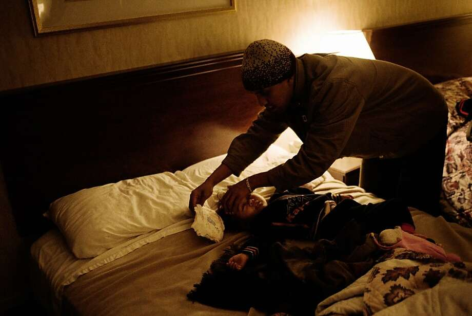 12/9/2009: Newark, New Jersey: A Karen youth, affected by disabities, whose temerature had risen all day, was cuddled by his father and ushered to sleep. Photo: Gabriele Stabile