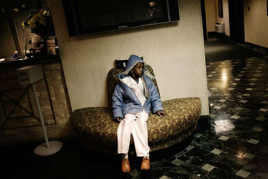 "12/11/2009, Newark, New Jersey: A somali boy waits in the lobby of the ""Refugee Hotel"" to be assigned a room for himself and his family. Many children wear clothes several sizes larger than them. Photo: Gabriele Stabile"