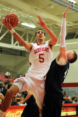 Sacred Heart's Justin Swidowski drives to the net over Yale's Greg Mangano during basketball action at Sacred Heart University, in Fairfield, Conn. Dec. 5th, 2011. Yale defeated SHU 73-71. Photo: Ned Gerard / Connecticut Post