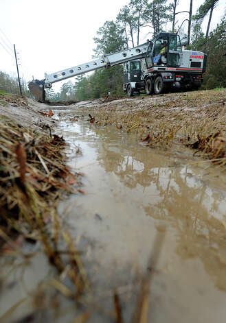 Jefferson County employees clear out a ditch on Tram Road Tuesday in preparation for today's weather that is expected to bring 3 to 6 inches of water and tropical-storm like winds. Photo taken Wednesday, January 08, 2013 Guiseppe Barranco/The Enterprise Photo: Guiseppe Barranco, STAFF PHOTOGRAPHER / The Beaumont Enterprise