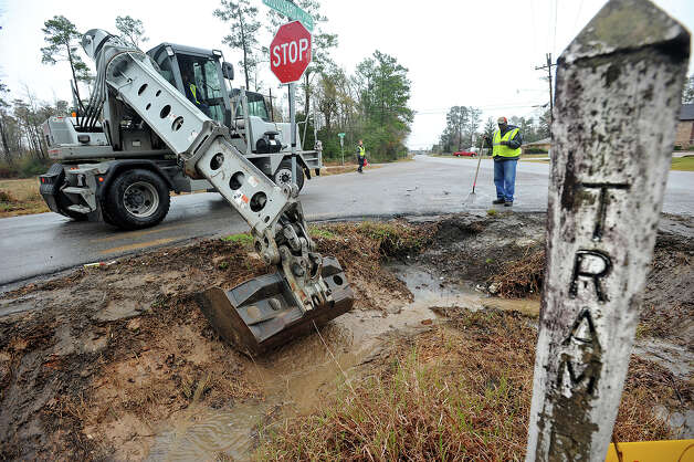 Beaumont employees clear out a ditch on Tram Road Tuesday in preparation for today's weather that is expected to bring 3 to 6 inches of water and tropical-storm like winds. Photo taken Wednesday, January 08, 2013 Guiseppe Barranco/The Enterprise Photo: Guiseppe Barranco, STAFF PHOTOGRAPHER / The Beaumont Enterprise