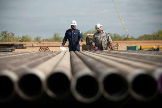 Rig workers inspect casings that will be loaded into the well in preparation for the hydraulic fracturing process at a Chesapeake Energy drill site in Dimmit, Texas in the Eagle Ford Shale. The Texas Tribune (Galbraith: Drilling). Credit: Tamir Kalifa for The Texas Tribune. Photo: Tamir Kalifa, For The Texas Tribune