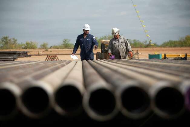 Rig workers inspect casings that will be loaded into the well in preparation for the hydraulic fracturing process at a Chesapeake Energy drill site in Dimmit County in the Eagle Ford Shale. The Texas Tribune (Galbraith: Drilling). Credit: Tamir Kalifa for The Texas Tribune. Photo: Tamir Kalifa, For The Texas Tribune