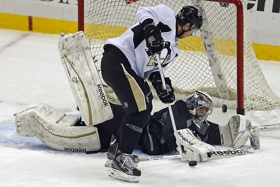 Penguins goalie Marc-Andre Fleury sprawls across the goal to block a shot by teammate James Neal in an informal workout. Photo: Gene J. Puskar, Associated Press