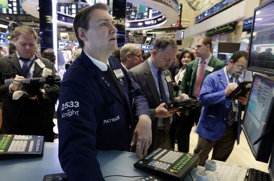 Specialist Patrick King, second left, works on the floor of the New York Stock Exchange Tuesday, Jan. 8, 2013. U.S. stocks opened mostly lower Tuesday as traders awaited the start of U.S. corporate earnings season. (AP Photo/Richard Drew) Photo: Richard Drew