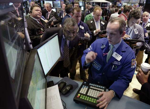Specialist Patrick Kelly, left, directs trading at his post on the floor of the New York Stock Exchange Tuesday, Jan. 8, 2013. U.S. stocks opened mostly lower Tuesday as traders awaited the start of U.S. corporate earnings season. (AP Photo/Richard Drew) Photo: Richard Drew