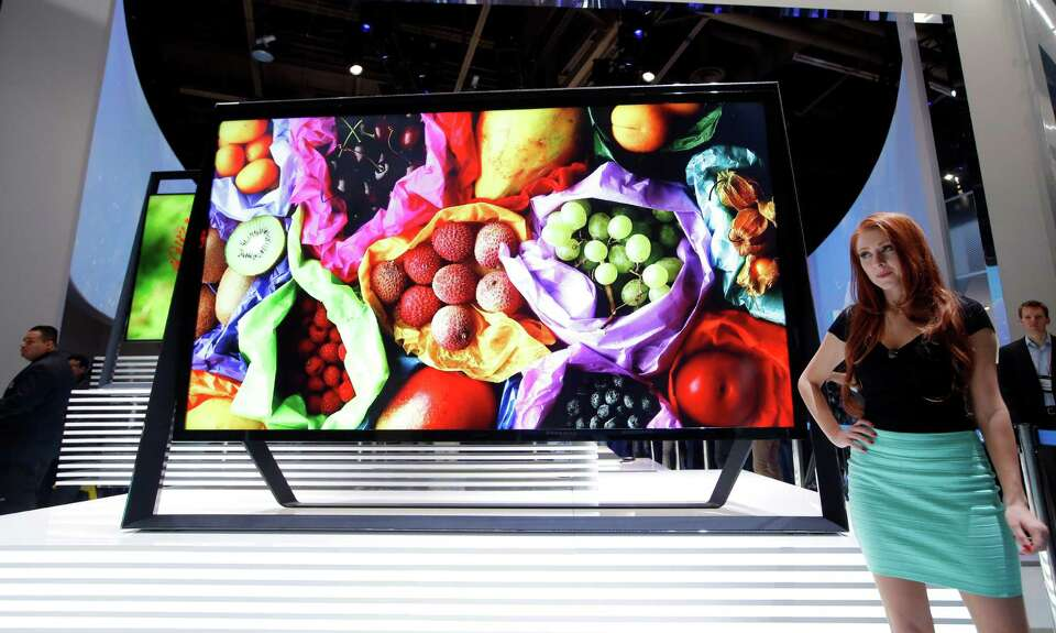 A model stands next to Samsung 110-inch 4k Ultra HD TV at the Samsung booth at the International Con